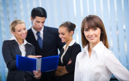 Foto de Portrait of happy smiling businesswoman and colleagues on background, at office - Imagen libre de derechos