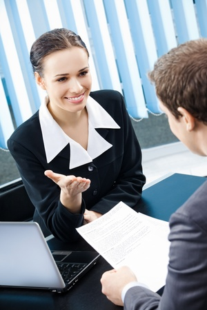 Two young happy smiling businesspeople, or business woman and client working with documents at office