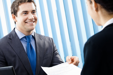Two young happy smiling businesspeople, or businessman and client working with documents at office