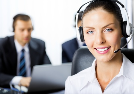 Portrait of happy smiling young female customer support phone operator in headset at office