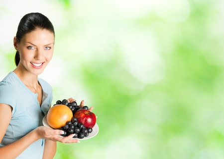 Young happy smiling woman with plate of fruits, outdoor. To provide maximum quality, I have made this image, by combination of two photos.You can use right part for slogan, big text or banner.