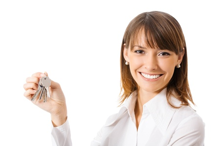 Young happy smiling business woman or real estate agent showing keys from new house, isolated on white background