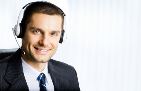 Portrait of happy smiling customer support phone operator in headset at office. You can use right part for slogan, text or banner.