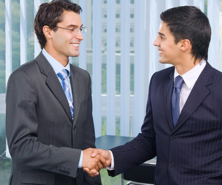 Two happy smiling businesspeople, or business man and client, handshaking at office
