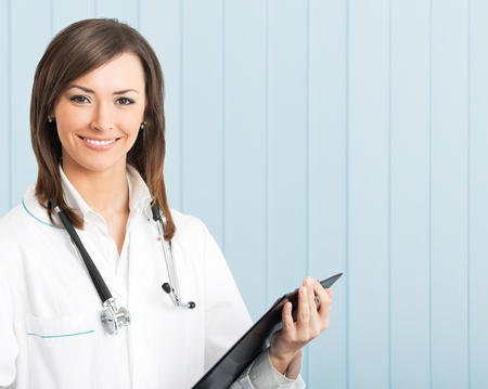 Portrait of happy young smiling female doctor with clipboard at office