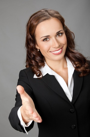 Portrait of young cheerful beautiful business woman giving hand for handshake, over grey background