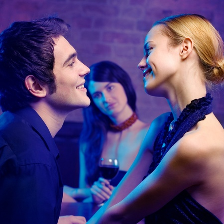 Young happy smiling couple and woman looking at them at club. Focus on couple.
