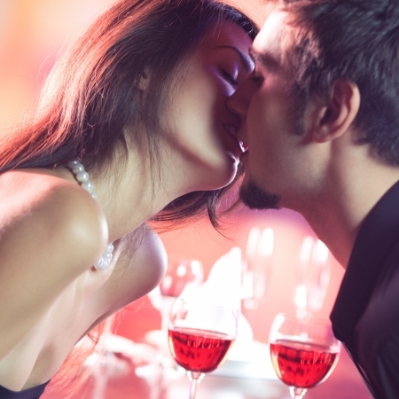 Young happy amorous couple kissing on romantic date, at restaurant