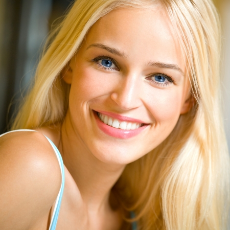 Portrait of happy cheerful smiling young beautiful blond woman, indoorsの写真素材