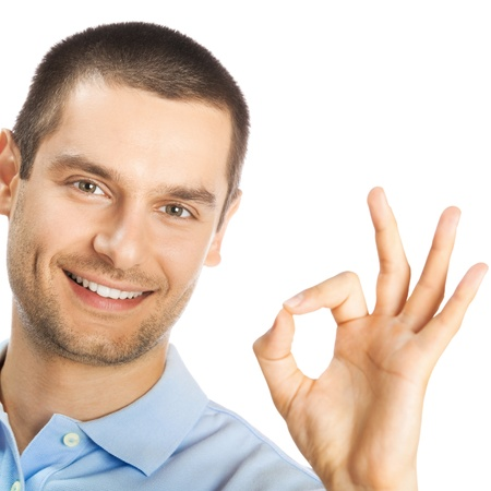 Portrait of cheerful young man showing okay gesture, isolated over white background