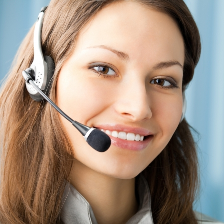 Young cheerful smiling support phone female operator in headset at office