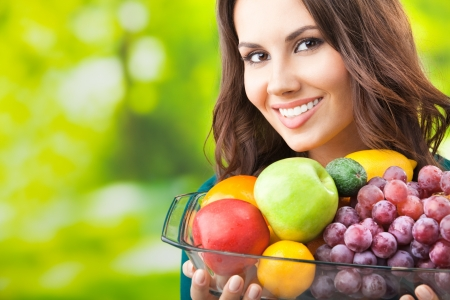 Young happy smiling woman with plate of fruits, outdoors, with copyspace for text or slogan.