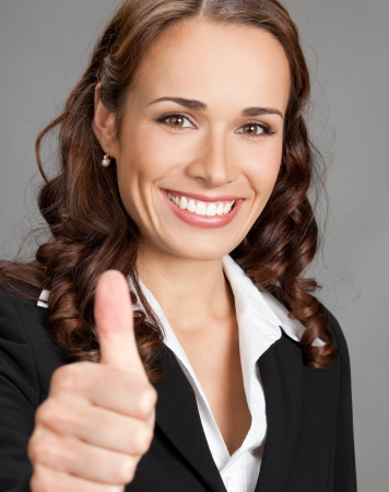 Happy smiling cheerful young business woman showing thumbs up gesture, over grey background