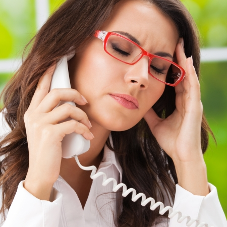 Thinking, tired or ill with headache business woman with phone at office