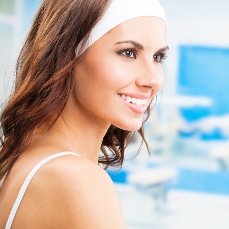 Portrait of young cheerful smiling woman at fitness club or gym