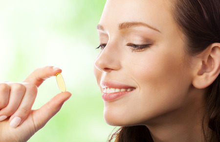 Portrait of woman with Omega 3 fish oil capsule, outdoors