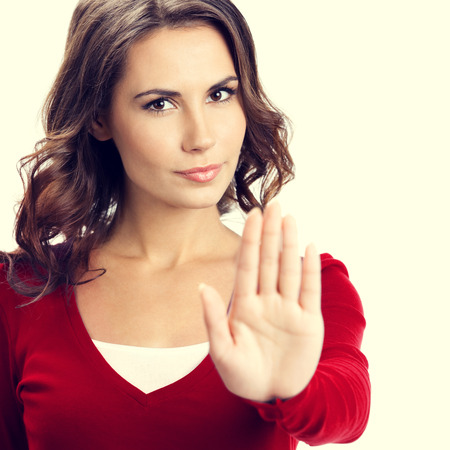Portrait of serious young woman showing stop gesture