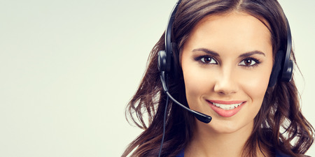 Portrait of cheerful young support phone operator or businesswomen in headset, with blank copyspace area for slogan or text. Customer service concept.