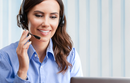 Portrait of happy smiling cheerful beautiful young female support phone operator in headset, at office, with blank copyspace area for slogan or text. Customer assistance service concept.