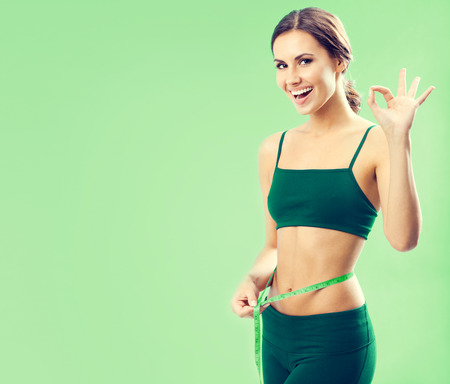 Portrait of smiling young lovely woman in fitness wear with tape, showing okay gesture, over green background, with blank copyspace area for text or slogan