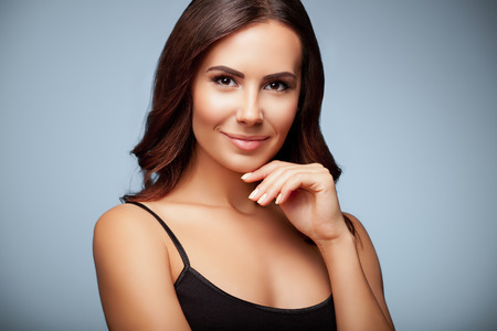 Photo pour portrait of thinking young woman in black tank top clothing, on grey background - image libre de droit