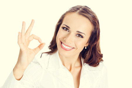 Happy smiling young business woman with okay gesture