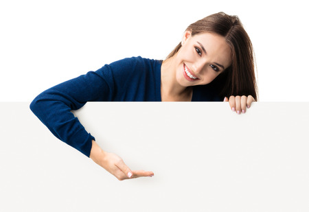 Portrait of happy smiling young woman in blue casual smart clothing, showing empty blank signboard with copyspace area for text or slogan, isolated against white background