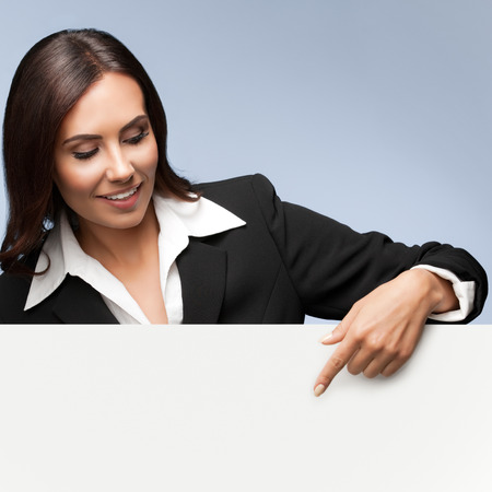 Foto per Portrait of happy smiling young businesswoman in black suit, showing blank signboard with blank copyspace area for slogan or text, over grey background - Immagine Royalty Free