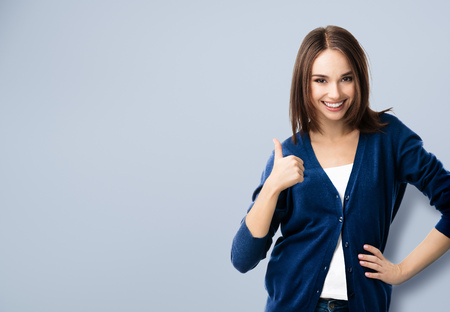 Photo for portrait of smiling beautiful young woman in casual smart blue clothing, showing thumbs up gesture, with copyspace for slogan or text message - Royalty Free Image