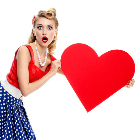 Woman holding heart symbol, dressed in pin-up style dress with polka dot, isolated over white. Caucasian blond model posing in retro fashion and vintage concept studio shoot.