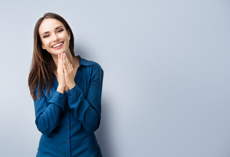 Photo pour Portrait of happy gesturing smiling young woman in casual smart blue clothing, on grey, with copyspace area for text or slogan - image libre de droit