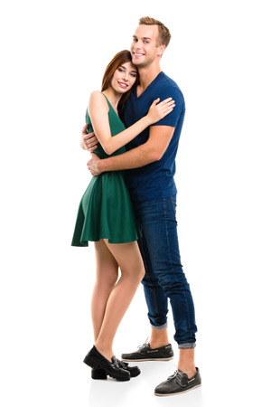 Photo pour Full body portrait of young happy hugging couple, standing close to each other and looking at camera with smile. Caucasian models in love, relationship, dating, flirting, lovers, romantic concept, isolated against white background. - image libre de droit