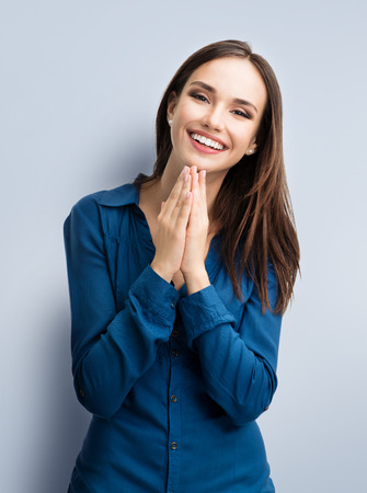 Portrait of happy gesturing smiling young woman in casual smart blue clothing, on grey background. Caucasian brunette model in emoshions and optimistic, positive, happy feeling concept studio shot.