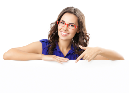 Foto de Happy smiling beautiful young woman in blue smart casual clothing and glasses, showing blank signboard or copyspace for slogan or text, isolated against white background - Imagen libre de derechos