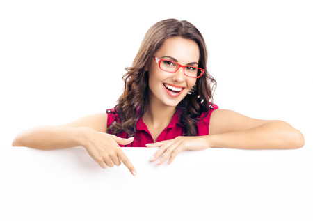Foto de Happy smiling beautiful young woman in red smart casual clothing and glasses, showing blank signboard or copyspace for slogan or text, isolated against white background - Imagen libre de derechos