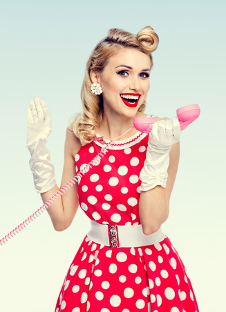 Photo for Bright photo of beautiful happy woman with phone, dressed in pin-up style red dress in polka dot and white gloves. Caucasian blond model posing in retro studio shoot. - Royalty Free Image