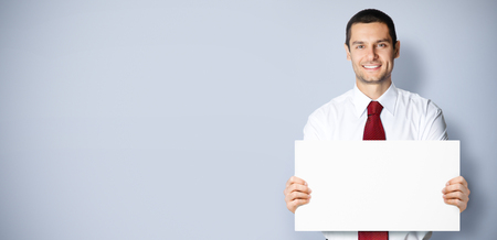 Photo for Business concept photo of businessman showing blank signboard, with empty copy space place for some text, advertising or slogan, over grey background - Royalty Free Image