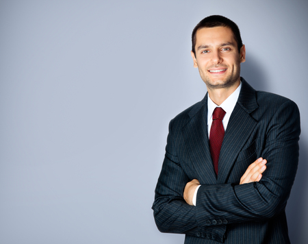 Photo pour Business concept photo of smiling confident businessman in black suit and red tie, with crossed arms pose, empty copy space place for some text, advertising or slogan, standing against grey background - image libre de droit