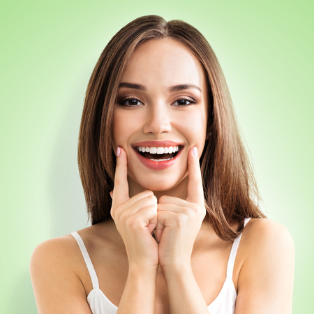 Photo for Portrait image of happy woman showing toothy smile, in casual clothing, over green color background. Optimistic, happiness and dental health concept photo. - Royalty Free Image