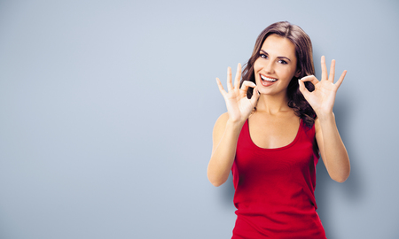 Photo pour Portrait photo - young happy smiling beautiful woman in casual clothing, showing okay gesture, or zero hand sign, over grey color wall background. Girl in red dress. Brunette excited model at studio. - image libre de droit