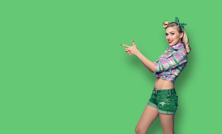 Photo pour Young happy smiling woman, dressed in pin-up style, showing something or copyspace area for advertise, slogan or text message. Caucasian blond model posing in retro fashion and vintage concept studio shoot, on green background. - image libre de droit
