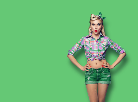 Foto per Excited surprised woman. Girl in pin up style, looking sideways. Blond model at retro fashion and vintage concept. Green color background. Copy space for some advertise slogan, imaginary or text. - Immagine Royalty Free