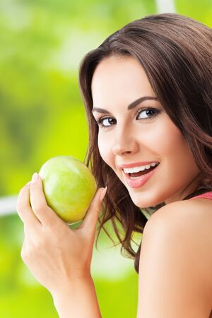 Photo for Young happy smiling attractive woman with green apple - Royalty Free Image