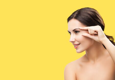 Photo for Skin care beauty concept. Portrait of smiling woman pointing brow or eye, touching skin, applying face cream, isolated over grey color background. Brunette model at studio shot. - Royalty Free Image
