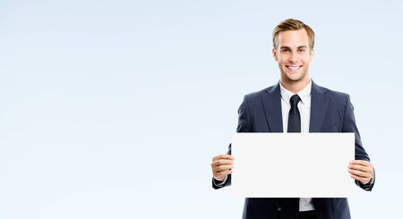 Happy businessman showing blank signboard, isolated against grey background. Empty copy space for some slogan or advertising tsign ext. Success in business concept picture.
