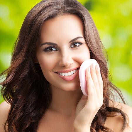 Photo pour Young lovely brunette woman cleaning skin by cotton pad - image libre de droit