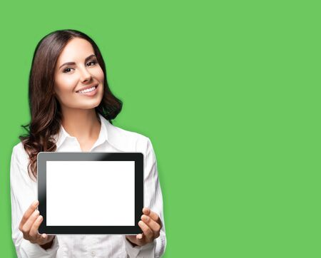 Photo pour Cheerful beautiful brunette confident businesswoman showing blank no-name tablet pc monitor, over green color background, with copy space area for some text. Success in business concept. - image libre de droit