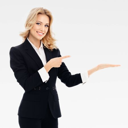 Photo pour Smiling businesswoman, showing, holding or giving something or copy space for some slogan or text, over grey background. Caucasian blond model in business or sales advertision concept. Square composition. - image libre de droit