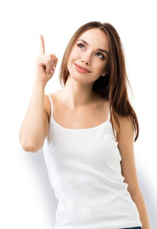 Photo for Smiling looking up brunette lovely woman showing something or copy space for some text or slogan, or making idea gesture, isolated against white background. - Royalty Free Image