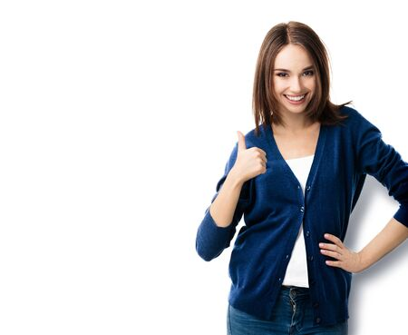 Photo pour Portrait of brunette lovely woman in casual smart blue clothing, showing thumbs up gesture, isolated against white background. Emoshions and optimistic, positive concept. - image libre de droit